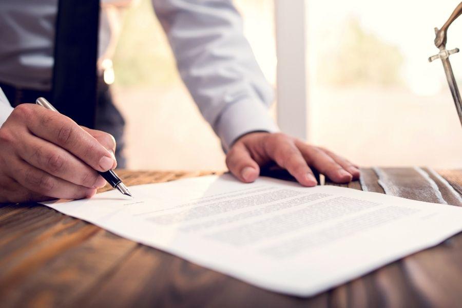 Cosa fa il notaio: uomo firma un documento notarile
