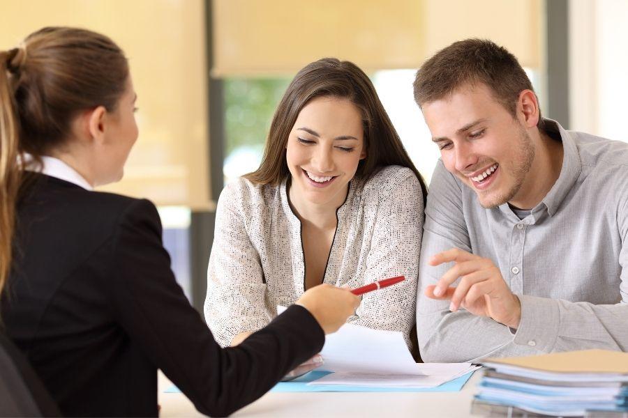 cosa fa il notaio al rogito: coppia felice riceve la penna dal notaio per sottoscrivere i documenti notarili del rogito.